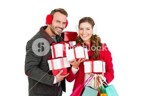 Happy young couple holding gifts and shopping bags