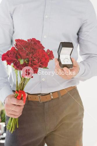 Happy young man holding engagement ring