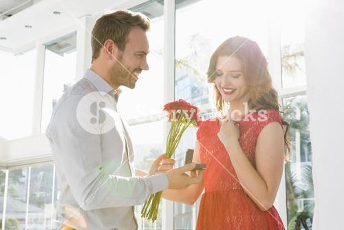 Man offering flowers and engagement ring