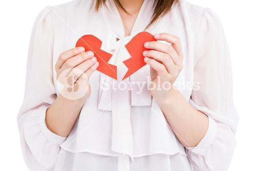 Young woman holding broken heart