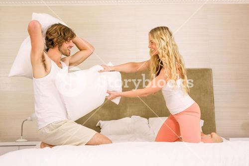 Cute couple pillow fighting on their bed