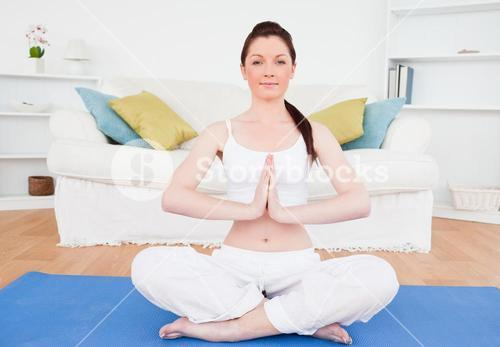 Good looking female doing yoga on a gym carpet