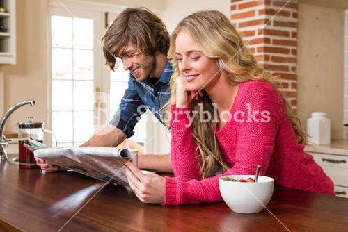 Cute couple reading the newspaper