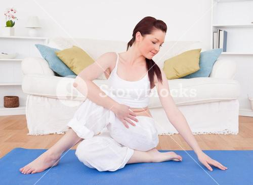 Good looking redhaired female stretching in the living room