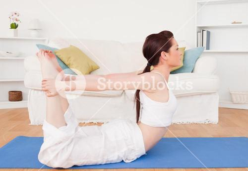 Young gorgeous redhaired female stretching in the living room