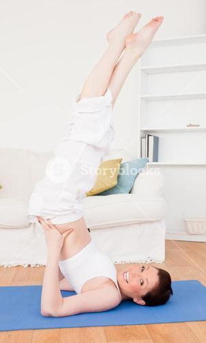 Young good looking redhaired female stretching in the living room