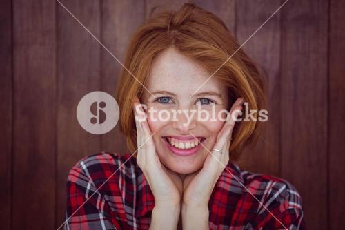 smiling hipster woman with her hands on her face