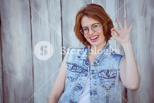 "smiling hipster woman giving the ""ok"" sign"