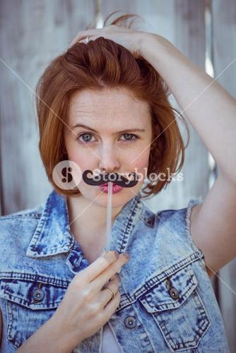 beautiful hipster woman holding a fake mustache