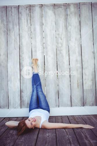 smiling hipster woman with her legs against the wall