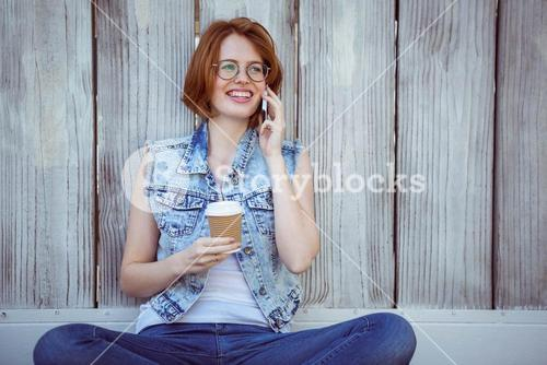 smiling hipster woman holding a coffee making a phonecall