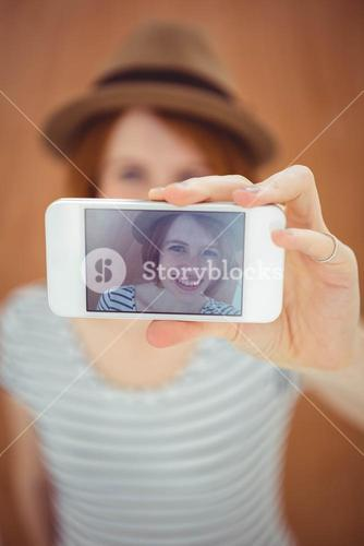smiling hipster woman taking a selfie