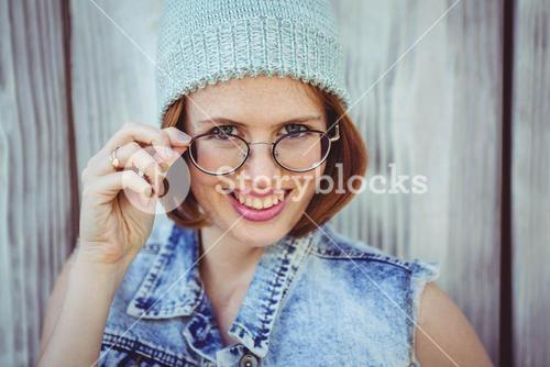 smiling hipster woman in glasses and a beanie hat
