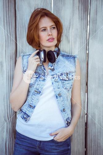 beautiful hipster woman wearing headphones and looking into the distance