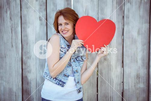 smiling hipster woman holding a carboard heart
