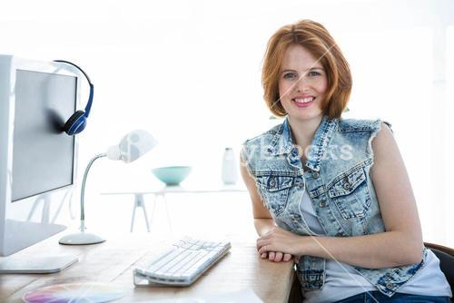 smiling hipster woman sitting at a desk