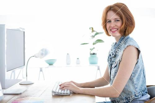 smiling hipster woman sitting at her computer