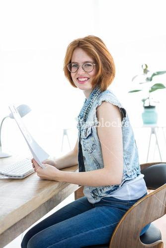 smiling hipster woman holding paperwork