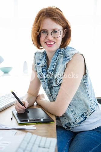 smiling hipster businesswoman writing on a digital drawing tablet