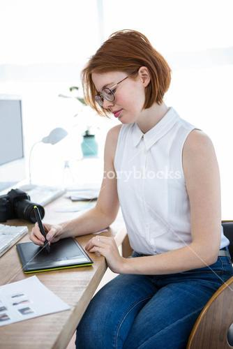 thoughtful hipster businesswoman with a digital drawing tablet