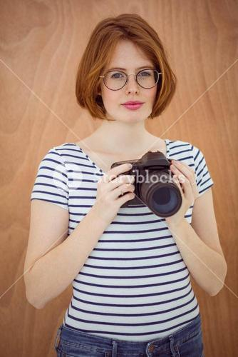 smiling hipster woman holding a digital camera
