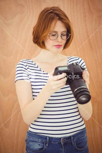 beautiful hipster woman looking at pictures on a digital camera