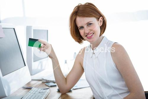 smiling hipster business woman holding up a credit card