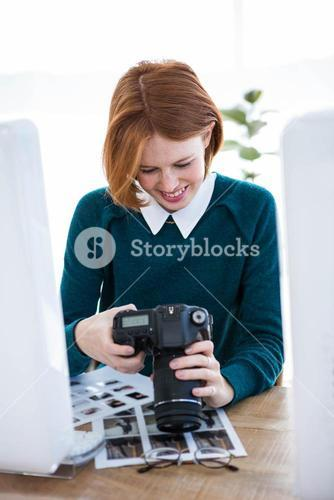 smiling hipster photographer looking at pictures on her camera