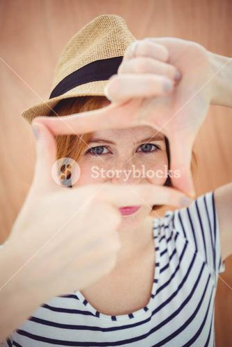 blue eyed hipster woman looking through her hand
