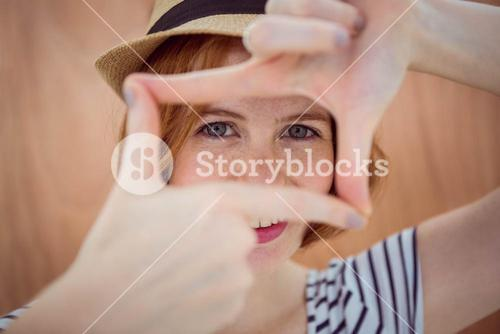 Blue eyed hipster looking through her hands