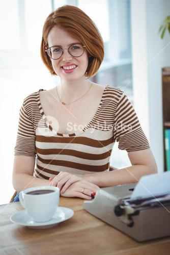 smiling hipster woman with coffee and a typewriter