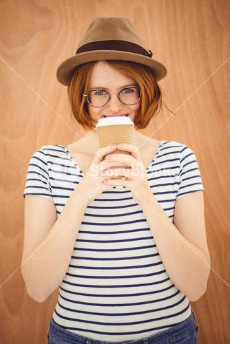 smiling hipster woman drinking a  cup of coffee