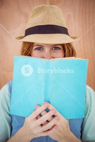 blue eyed hipster woman looking over the top of a book
