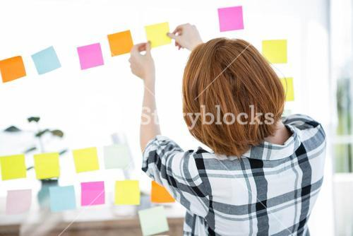 hipster woman sticking up coloured paper squares