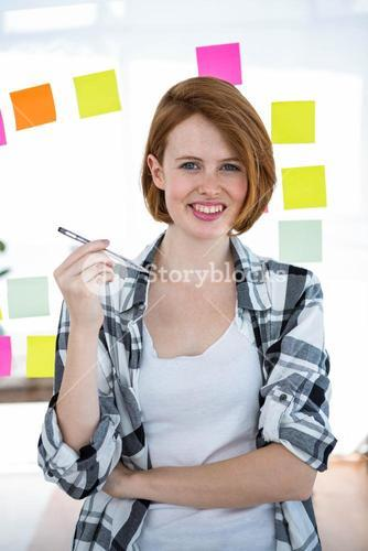 smiling hipster woman holding a pen in her hand