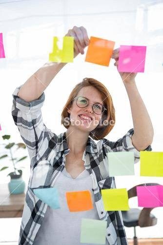smiling hipster woman sticking notes on a notice board