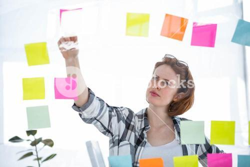 thoughtful hipster woman brainstorming over notes