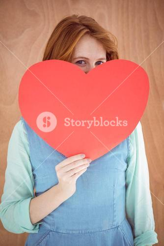 Young hipster holding a red heart shape