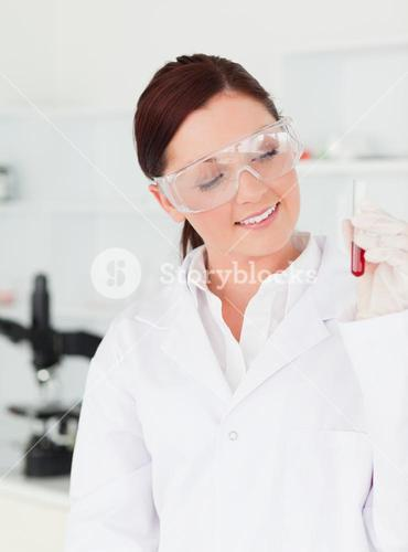 Pretty redhaired scientist looking at the camera while holding a test tube