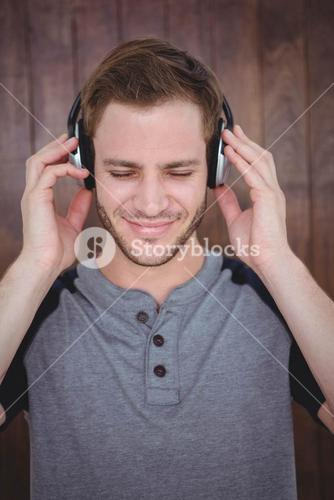 Handsome hipster listening to music with headphones