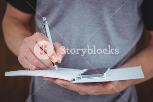 Masculine hands writing on notebook