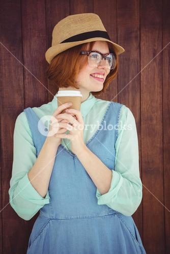 Cute red haired hipster with glasses holding disposable cup