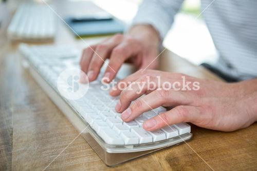 Masculine hands typing on keyboard