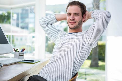 Handsome businessman relaxing on his desk chair