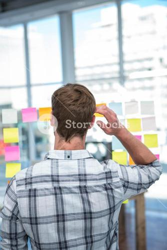 Worried hipster man in front of post-it