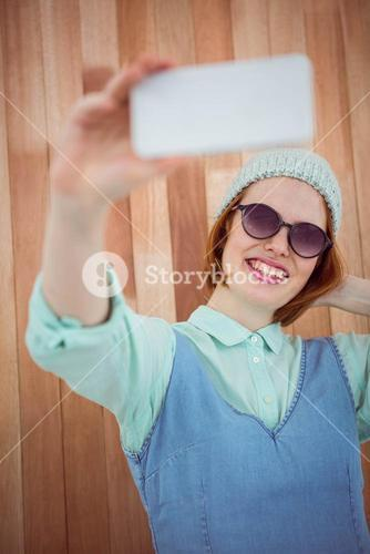 Red haired hipster taking selfie