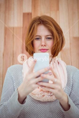 Red haired hipster using smartphone