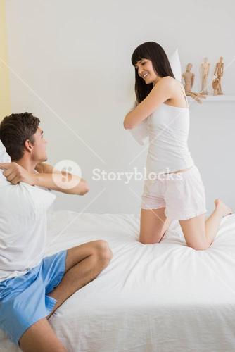 Young couple playing pillow fight
