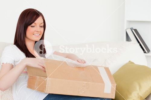 Attractive redhaired woman opening a carboard box while sitting on a sofa