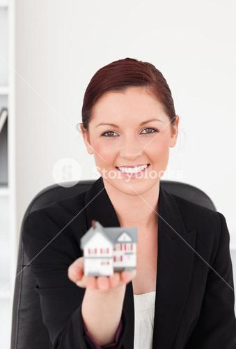 Attractive redhaired woman in suit holding a miniature house